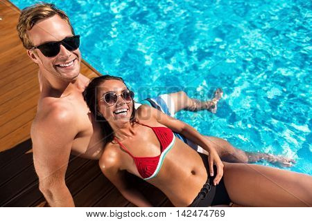 Pleasant moment. Cheerful content couple smiling and sitting near swimming pool while expressing joy