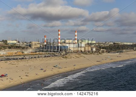 Los Angeles, California, USA - August 6, 2016:  Aerial view of Dockweiler State Beach, LADWP Scattergood power plant and oil refinery tanks on an industrial section of the California coast.