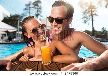 Involved in positivity. Delighted overjoyed loving couple smiling and drinking cocktail while having fun in the swimming pool