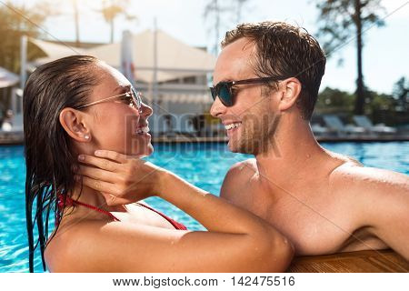 Spend time together. Overjoyed delighted couple standing in the swimming pool and looking at each other while having fun
