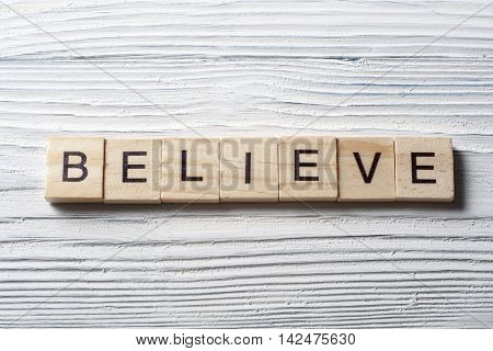 BELIEVE word written on wood block. Wooden ABC