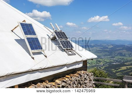 Portable solar panels on the roof of a house in the mountains.