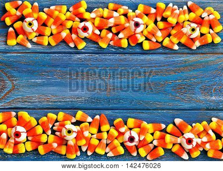Halloween candy corns and candy eyeball on blue wooden background