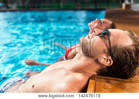 Revel in sunny days. Pleasant delighted loving couple lying in the swimming pool and resting