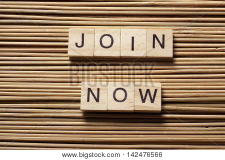 Join now on wooden abc cube at wood background.