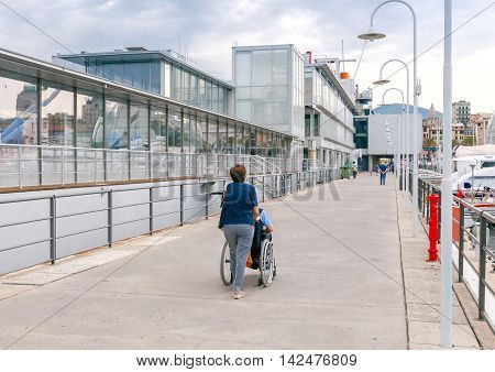 A woman carries a disabled person in a wheelchair on the waterfront in the city of Genoa.