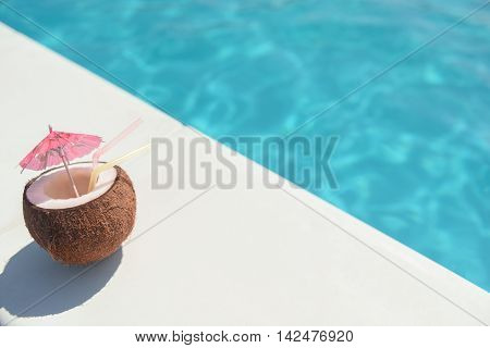 Close up of cocktail in coconut with straws and small umbrella near swimming pool
