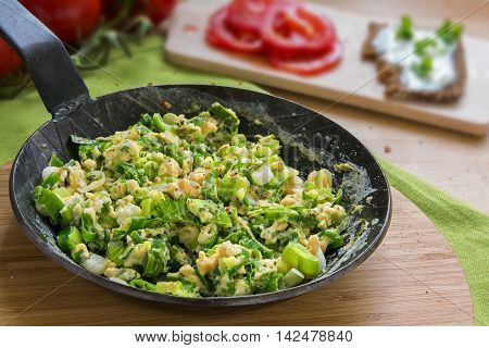 Scrambled eggs with spring onions in a black frying pan on a rustic wooden board selected focus narrow depth of field