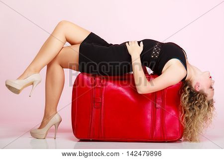 Full length of young elegant lady in voyage traveler woman with old red suitcase luggage bag on pink background. Travel theme