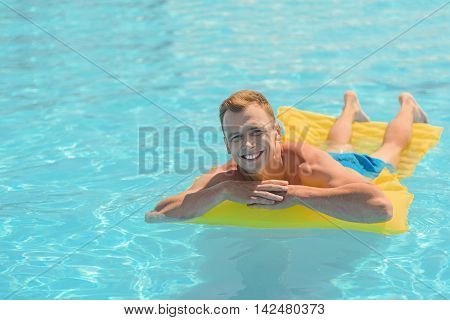 Happy young man is relaxing on air mattress on blue water. He is looking at camera and smiling