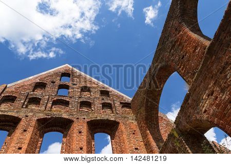detail of the monastery ruin of brick masonry with gable and window arches against the blue sky with clouds Bad Doberan northern Germany