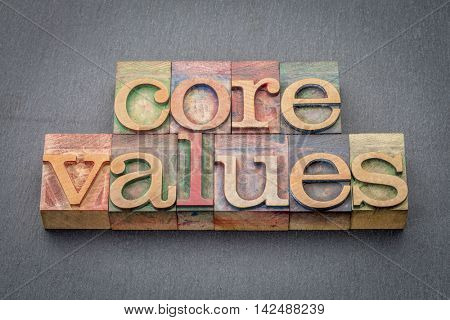 core values  banner  - word abstract in  letterpress wood type blocks stained by color inks against a slate stone
