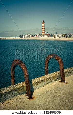 Pier with a pair of rusty handrails of a ladder with lighthouse in the background