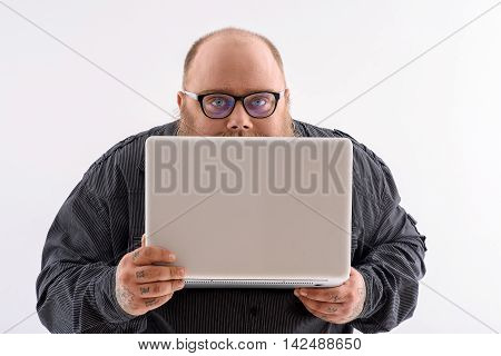 Fat smart man is working on laptop. He is holding technology and peeping through it with interest. Isolated