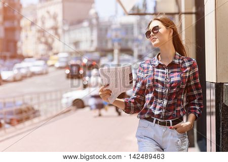 Confident young woman is holding newspaper and waving it near her face. She is standing and putting hand in pocket