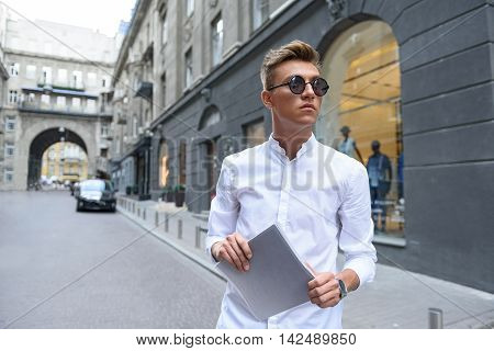 Smart young man is walking in city. She is holding book and looking forward with seriousness