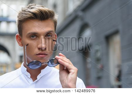 Confident young man is looking at camera seriously. He is standing on street and wearing his glasses
