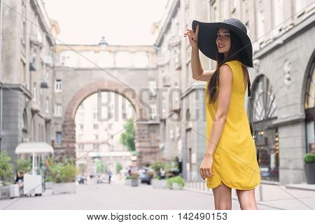 Joyful young girl is having walk in city. She is looking back flirtingly. Lady is touching her sunhat and smiling
