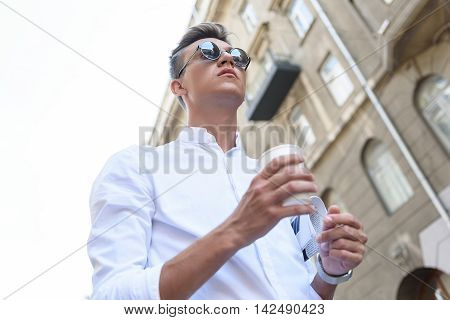 Low angle of young man drinking coffee on street. He is standing and carrying newspaper. Man is looking forward with confidence