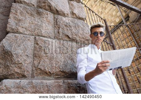 Serious young man is reading newspaper outdoors. He is standing near wall