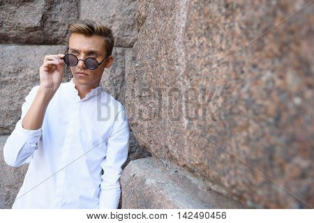 Confident guy is standing and leaning on stone wall. He is adjusting his glasses and looking forward with seriousness