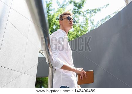Dreamful young guy is standing on balcony and relaxing. He is holding tablet and looking forward pensively