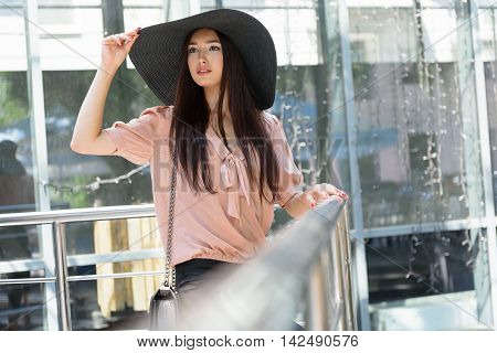 Pretty girl is waiting for someone on balcony. She is standing and touching her black sunhat. Lady is looking forward with hope