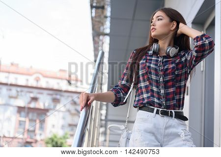 Relaxed young woman is going down stairs. She is touching railing and looking at city with enjoyment