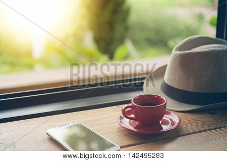 Coffee With Hat And Smart Phone On Coffee Shop Table