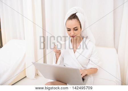 Attractive girl is entertaining with laptop at beauty salon. She is sitting on bed in bathrobe and towel. Lady is drinking coffee and relaxing