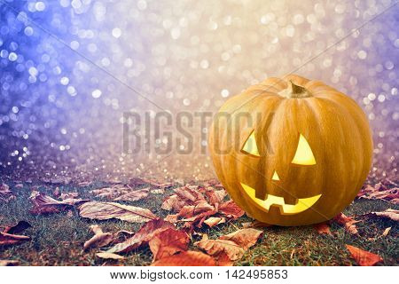 Halloween background with pumkin jack lantern on grass with autumn leaves
