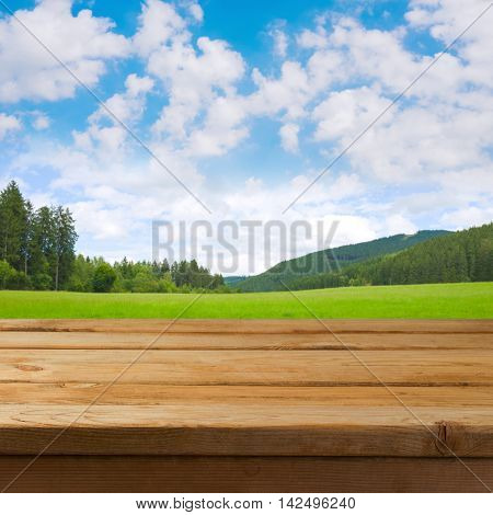 Empty wooden deck table over nature landscape meadow background