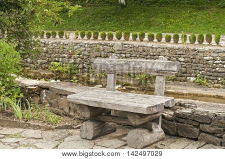 Vintage wooden bench on stoned river bank alley