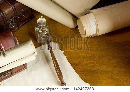 Vintage scrolls and tools for writing in ink on a wooden table