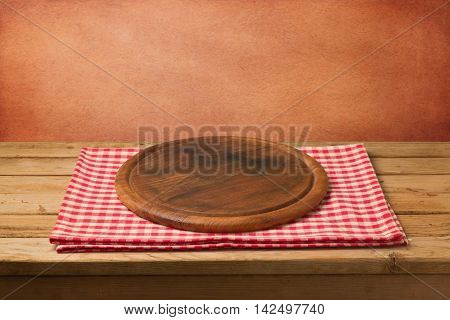 Empty wooden table with cutting board on checked tablecloth