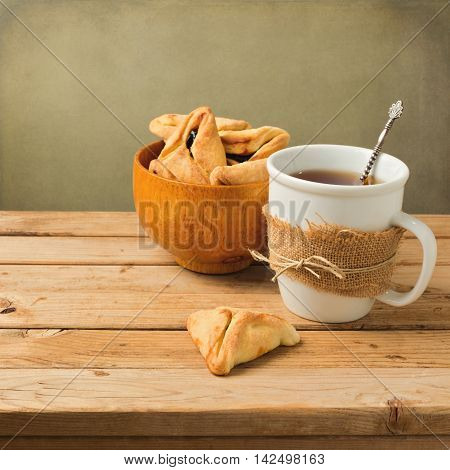 Hamantaschen cookies with cup of tea on wooden table