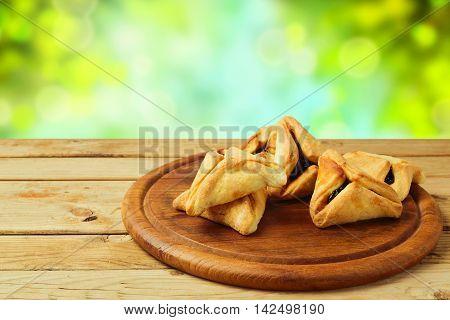 Hamantaschen cookies on wooden table over bokeh background
