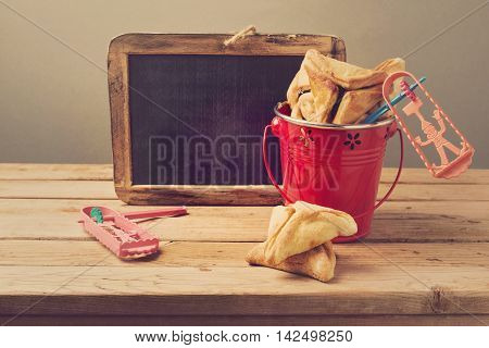 Hamantaschen cookies in bucket with grogger and chalkboard
