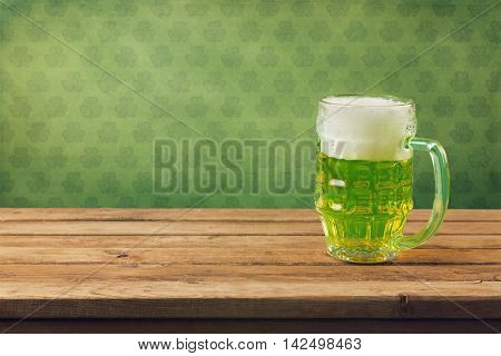 St. Patricks's day background. Beer on wooden table over retro wallpaper with shamrock