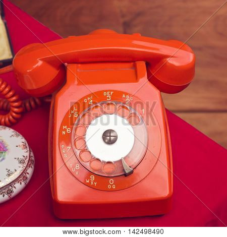 Vintage red rotary telephone on table with cloth