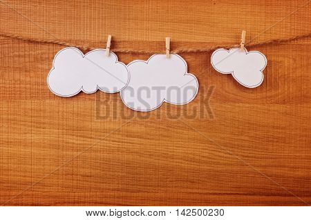 Paper white clouds hanging over wooden board
