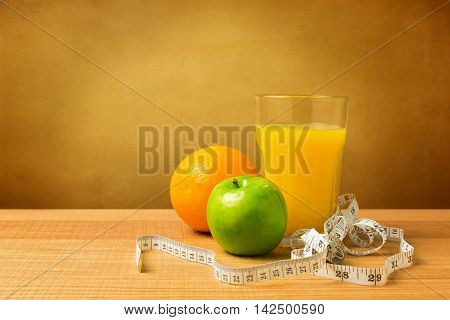 Diet concept. Orange juice and apple on wooden table