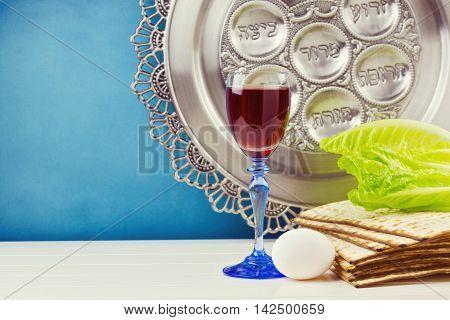Jewish Passover holiday celebration background with wine, egg and matzos