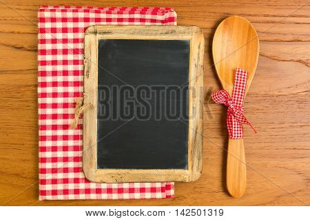 Chalkboard with wooden spoon on tabletop with tablecloth