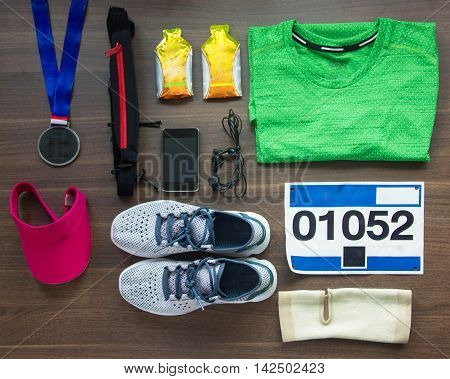 Top View Running Shoes Marathon Race Bib (number) Medal Runners Gear And Energy Gels On Wood Background Sport Fitness And Healthy Lifestyle Concept.