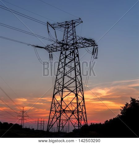 Electricity pylons power lines sky at sunset.
