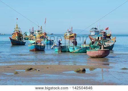 MUI NE, VIETNAM - DECEMBER 25, 2015: Fishermen prepare their boats after a night of fishing. Historical landmark of the Vietnam