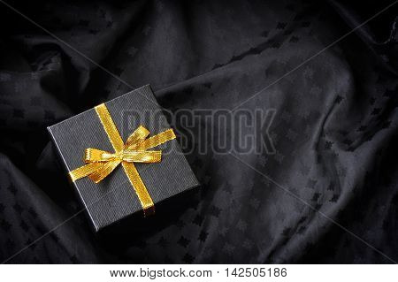 black gift box with golden ribbon bow on black silk textured fabric