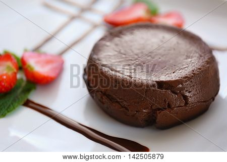Chocolate fondant with strawberry on plate, closeup