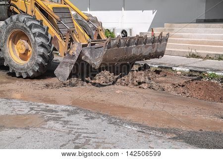 Excavator working on the Repair of pipe water and sewerage on road Worker using dig a hole to fix a water.